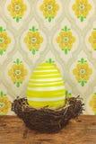 Κίτρινο βαμμένο μεγάλο αυγό Πάσχας σε μια φωλιά πουλιών σε έναν ξύλινο πίνακα Στοκ εικόνα με δικαίωμα ελεύθερης χρήσης