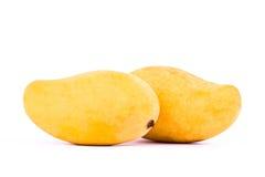 Κίτρινο γλυκό ώριμο μάγκο δύο στα άσπρα τρόφιμα φρούτων υποβάθρου υγιή που απομονώνονται Στοκ Εικόνες