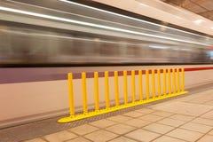 Κίτρινο εμπόδιο ασφάλειας στην πλατφόρμα του υπογείου ως θολωμένη εικόνα Στοκ Εικόνες