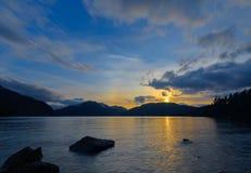 Κίτρινο ηλιοβασίλεμα πέρα από τα βουνά δίπλα στη λίμνη Στοκ Εικόνα