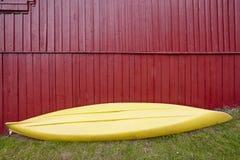 Κίτρινο καγιάκ πέρα από μια κόκκινη ξύλινη πρόσοψη καμπινών Αθλητισμός περιπέτειας Στοκ εικόνα με δικαίωμα ελεύθερης χρήσης