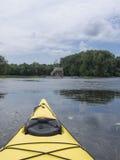 Κίτρινο καγιάκ στον ποταμό που εξετάζει την επιφυλακή στοκ φωτογραφίες