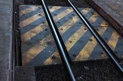 Κίτρινο και άσπρο σημάδι γραμμών στην προειδοποίηση διαδρομής σιδηροδρόμων ενώ περίπατος απέναντι στο σιδηροδρομικό σταθμό Lampan Στοκ Εικόνες