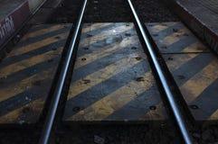 Κίτρινο και άσπρο σημάδι γραμμών στην προειδοποίηση διαδρομής σιδηροδρόμων ενώ περίπατος απέναντι στο σιδηροδρομικό σταθμό Lampan Στοκ εικόνα με δικαίωμα ελεύθερης χρήσης