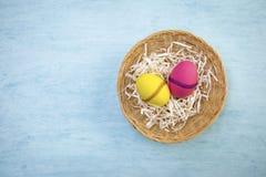 Κίτρινο και κόκκινο αυγό Πάσχας στο στρογγυλό καλάθι ινδικού καλάμου Στοκ εικόνες με δικαίωμα ελεύθερης χρήσης