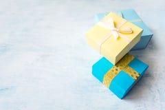 κίτρινο και μπλε κιβώτιο δώρων τρία με την άσπρη κορδέλλα και τόξο στο ligh στοκ φωτογραφίες με δικαίωμα ελεύθερης χρήσης
