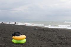 Κίτρινο και πράσινο επιπλέον δαχτυλίδι στην παραλία, συννεφιασμένος, σύννεφα, κύματα στοκ εικόνα με δικαίωμα ελεύθερης χρήσης