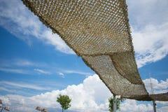 Κίτρινο καφετί sunshade ενάντια στο νεφελώδη μπλε ουρανό στοκ φωτογραφίες με δικαίωμα ελεύθερης χρήσης
