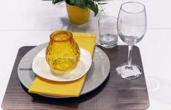Κίτρινο κηροπήγιο γυαλιού σε ένα άσπρο κύμβαλο και μια κίτρινη πετσέτα στοκ εικόνα με δικαίωμα ελεύθερης χρήσης