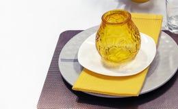 Κίτρινο κηροπήγιο γυαλιού σε ένα άσπρο κύμβαλο και μια κίτρινη πετσέτα στοκ φωτογραφία με δικαίωμα ελεύθερης χρήσης