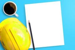 Κίτρινο κράνος ασφάλειας, η Λευκή Βίβλος, φλιτζάνι του καφέ και μαύρο penci στοκ φωτογραφίες