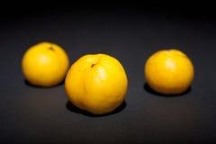 Κίτρινο κυδώνι τρία σε ένα μαύρο υπόβαθρο Στοκ Εικόνες