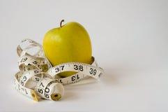 Κίτρινο μέτρο μήλων και ταινιών σχετικά με το άσπρο υπόβαθρο Στοκ Εικόνα