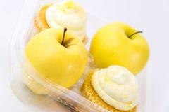 Κίτρινο μήλο εναντίον του κίτρινου cupcake Στοκ φωτογραφία με δικαίωμα ελεύθερης χρήσης