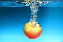 Κίτρινο μήλο στον παφλασμό νερού πέρα από το μπλε Στοκ φωτογραφία με δικαίωμα ελεύθερης χρήσης