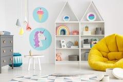 Κίτρινο μαξιλάρι πουφ στο ζωηρόχρωμο εσωτερικό δωματίων παιδιών ` s με τους λαμπτήρες και pos στοκ εικόνα