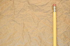 κίτρινο μολύβι σε μια ανακυκλωμένη τσαλακωμένη επιφάνεια εγγράφου Στοκ Φωτογραφία