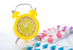 Κίτρινο ξυπνητήρι και ιατρικό πακέτο φουσκαλών Στοκ Φωτογραφία