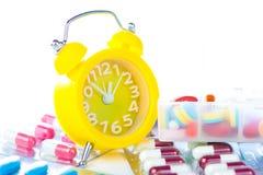 Κίτρινο ξυπνητήρι και ιατρικό πακέτο φουσκαλών Στοκ Εικόνες