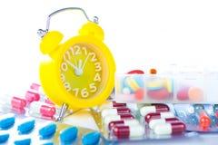 Κίτρινο ξυπνητήρι και ιατρικό πακέτο φουσκαλών Στοκ εικόνα με δικαίωμα ελεύθερης χρήσης