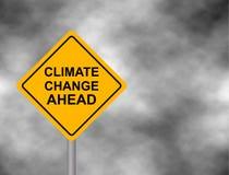 Κίτρινο οδικό σημάδι κινδύνου με το μήνυμα κλιματικής αλλαγής μπροστά Bord που απομονώνεται σε ένα γκρίζο υπόβαθρο ουρανού επίσης Στοκ Εικόνες