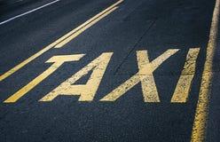 Κίτρινο οδικό σημάδι στην άσφαλτο - σημάδι ταξί Στοκ εικόνες με δικαίωμα ελεύθερης χρήσης