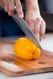 Κίτρινο πιπέρι κουδουνιών που κόβεται σε έναν ξύλινο πίνακα Στοκ Εικόνες