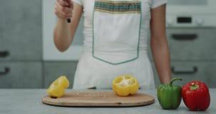 Κίτρινο πιπέρι που κόβεται σε σε αργή κίνηση σε μια σύγχρονη κουζίνα με το μεγάλο μαχαίρι από μια γυναίκα αρχιμαγείρων απόθεμα βίντεο