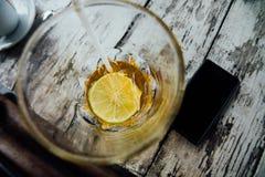 Κίτρινο ποτό με τον πάγο και ασβέστης στο γυαλί και το smartphone Κίτρινο κοκτέιλ με τον πάγο Στοκ φωτογραφίες με δικαίωμα ελεύθερης χρήσης