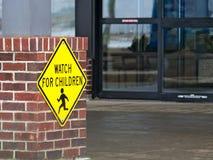 Κίτρινο ΡΟΛΟΙ ΓΙΑ το οδικό σημάδι ΠΑΙΔΙΩΝ κοντά σε ένα κτήριο στοκ φωτογραφίες με δικαίωμα ελεύθερης χρήσης