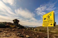 Κίτρινο σημάδι που δείχνει προς την καμπίνα επιβίωσης στο βουνό κοντά σε Trolltunga σε Odda, Νορβηγία Στοκ Φωτογραφία
