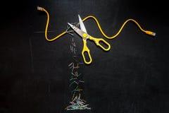 Κίτρινο σκοινί μπαλωμάτων που κόβεται από το ψαλίδι, σύνθεση που απομονώνεται πέρα από το μαύρο υπόβαθρο πινάκων κιμωλίας Στοκ Εικόνα