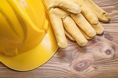 Κίτρινο σκληρό ζευγάρι καπέλων των λειτουργώντας γαντιών στο ξύλινο κατασκεύασμα πινάκων Στοκ Φωτογραφίες