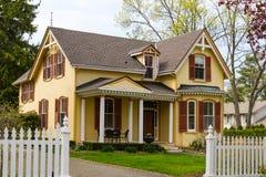 Κίτρινο σπίτι και άσπρος φράκτης στύλων στοκ εικόνα με δικαίωμα ελεύθερης χρήσης