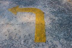 Κίτρινο σύστημα σηματοδότησης βελών κυκλοφορίας σε έναν δρόμο τσιμέντου Στοκ Εικόνα