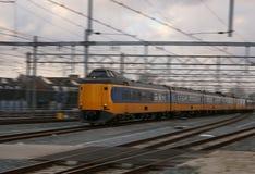 Κίτρινο τραίνο ή intercity οδήγηση πολύ γρήγορα με τη θαμπάδα κινήσεων, φυσ στοκ φωτογραφία με δικαίωμα ελεύθερης χρήσης