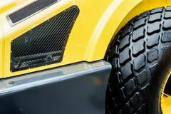 Κίτρινο τρακτέρ με μια μεγάλη ρόδα Στοκ φωτογραφίες με δικαίωμα ελεύθερης χρήσης
