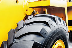 Κίτρινο τρακτέρ με μια μεγάλη ρόδα Στοκ Εικόνες