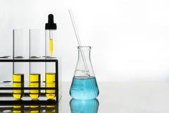 Κίτρινο υγρό στους σωλήνες δοκιμής και dropper, μπλε υγρό στη φιάλη Στοκ εικόνα με δικαίωμα ελεύθερης χρήσης