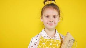 Κίτρινο υπόβαθρο, κορίτσι αρχιμαγείρων στην κίτρινη ποδιά με τα εργαλεία κουζινών φιλμ μικρού μήκους