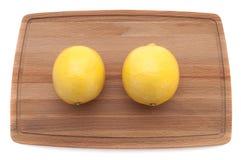 Κίτρινο φωτεινό juicy λεμόνι δύο σε μια ξύλινη τέμνουσα τοπ άποψη πινάκων στοκ εικόνα