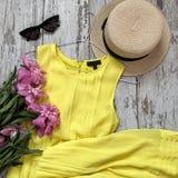 Κίτρινο φόρεμα με τα λουλούδια σε ένα ξύλινο υπόβαθρο στοκ φωτογραφίες με δικαίωμα ελεύθερης χρήσης