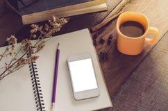 Κίτρινο φλυτζάνι καφέ με eyeglass βιβλίων το έξυπνο τηλέφωνο σημειωματάριων και μολύβι στον ξύλινο πίνακα - τονίστε τον τρύγο Στοκ Φωτογραφία