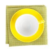 Κίτρινο φλυτζάνι καφέ πέρα από την πετσέτα κουζινών Στοκ Φωτογραφίες