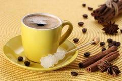 Κίτρινο φλυτζάνι με τον καφέ, ζάχαρη, φασόλια καφέ, κανέλα, anis αστεριών Στοκ εικόνα με δικαίωμα ελεύθερης χρήσης