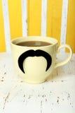 Κίτρινο φλυτζάνι με το έγγραφο mustache και καφές στο άσπρο ξύλινο υπόβαθρο Στοκ φωτογραφίες με δικαίωμα ελεύθερης χρήσης