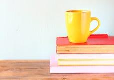 Κίτρινο φλυτζάνι του coffe στα παλαιά εκλεκτής ποιότητας βιβλία Στοκ Εικόνες