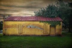 Κίτρινο χρωματισμένο κτήριο τούβλου με την οξυδωμένη κόκκινη στέγη μετάλλων στοκ φωτογραφία με δικαίωμα ελεύθερης χρήσης