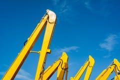 Κίτρινο backhoe με τον υδραυλικό βραχίονα εμβόλων ενάντια στο σαφή μπλε ουρανό Βαριά μηχανή για την ανασκαφή στο εργοτάξιο οικοδο στοκ εικόνες