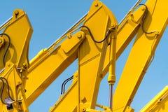 Κίτρινο backhoe με τον υδραυλικό βραχίονα εμβόλων ενάντια στο σαφή μπλε ουρανό Βαριά μηχανή για την ανασκαφή στο εργοτάξιο οικοδο στοκ φωτογραφία με δικαίωμα ελεύθερης χρήσης